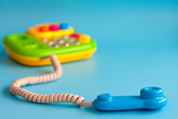 Colorful plastic toy mobile phone on a blue background for children