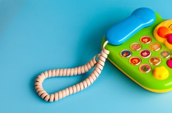 Colorful plastic toy mobile phone on a blue background for children.