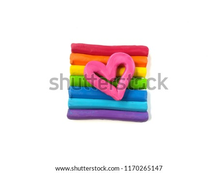 Colorful plasticine clay sticiks arrange rainbow colors with pink heart on top placed on white background, cute shape dough #1170265147