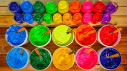 colorful Plastisol ink on pine wood table. Plastisol ink useful in tee shirt factory and in industry for export