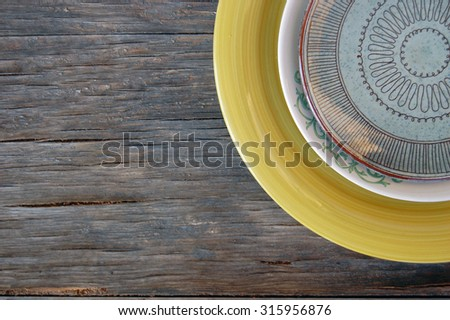 colorful plates on rustic wooden background