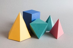 Colorful platonic solids, abstract geometric figures on gray background. Pyramid prism rectangular cube yellow blue pink green colored shapes. Shallow depth of field, copy space.