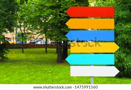 Colorful pointers on the background of the city park. Signpost directional arrows. Direction sign, empty frame #1475991560