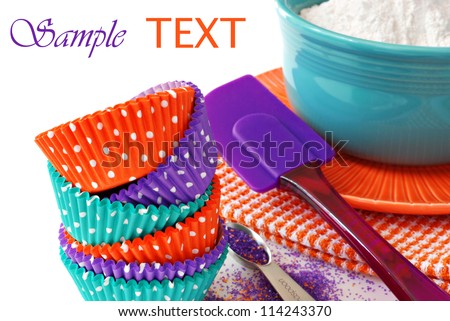 Colorful polka dot cupcake wrappers with color coordinated baking supplies on white background with copy space.  Closeup with shallow dof.