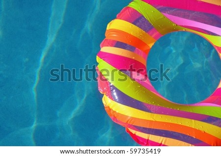 Colorful pool float / ring in swimming pool. Room for your text. - stock photo