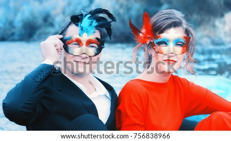Colorful portrait of a young enamored couple in masquerade masks - man in a suit and woman in red against a blue lake. Focus on foreground.