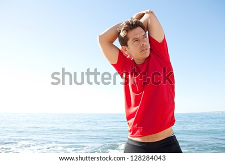 Colorful portrait of an attractive sports man stretching his arms and back while standing near the sea against a bright blue sky.