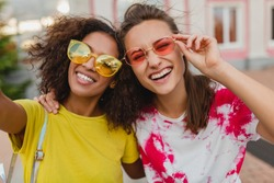 colorful portrait of happy young girls friends smiling sitting in street taking selfie photo on mobile phone, women having fun together, summer hipster fashion style, smiling, sunglasses accessories