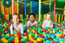 Colorful  portrait of three happy little kids in ball pit smiling happily at camera while having fun in children play center, copy space