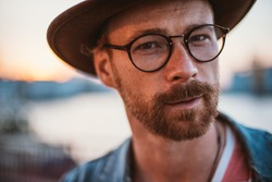 Colorful portrait of young handsome man with red beard in round glasses and in hat looking at camera during sunset outdoors