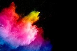 Colorful powder explosion on black background. Abstract pastel color dust particles splash.