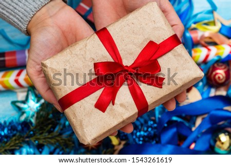 Colorful present gift present box in hands on toys background.
