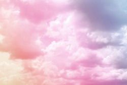 Colorful puffy fluffy cloud & cotton candy cloudscape on sunrise or sunset sky in tropical summer or spring sunlight & sun ray with gradient colors of blue, pink, purple, white & gray, surreal concept