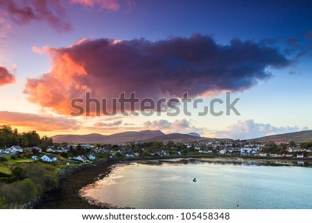 Colorful purple cloudscape at sunset  over a village