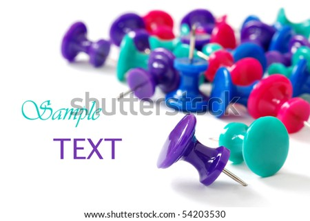 Colorful push pins on white background with copy space.  Macro with extremely shallow dof.