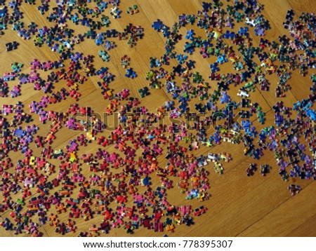colorful puzzle parts lying on a wooden floor #778395307