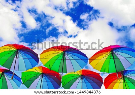 colorful rainbow bright umbrellas  street decoration against a blue sky with fluffy clouds #1449844376