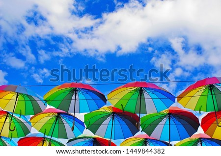 colorful rainbow bright umbrellas  street decoration against a blue sky with fluffy clouds #1449844382