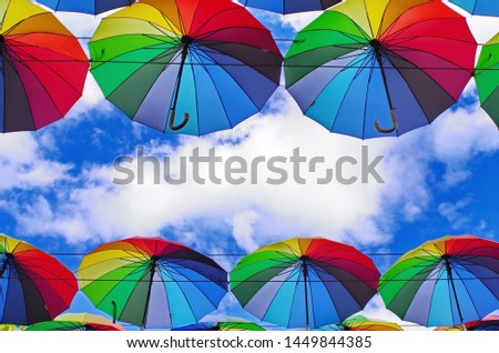 colorful rainbow bright umbrellas  street decoration against a blue sky with fluffy clouds #1449844385