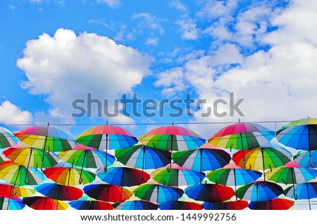 colorful rainbow bright umbrellas  street decoration against a blue sky with fluffy clouds #1449992756