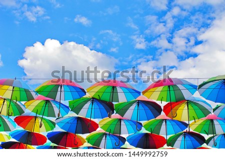 colorful rainbow bright umbrellas  street decoration against a blue sky with fluffy clouds #1449992759