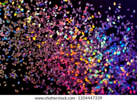 Colorful rainbow glitter / confetti rhombuses on a black background, top view. Perfect for carnival, night party invitation or festive background #1204447339