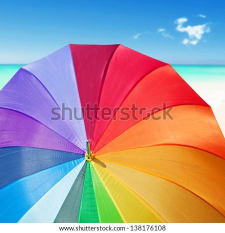 Colorful rainbow umbrella on a tropical beach