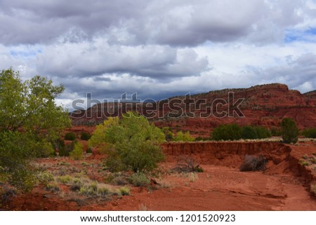 colorful red rock  desert wash and eroded hillside on a stormy fall day near jemez springs, new mexico
