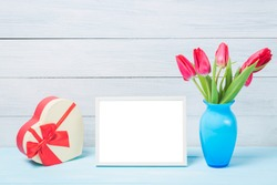Colorful red spring tulip flowers in nice blue vase and blank photo frame with decorative heart giftbox on light wooden background as greeting card. Mothersday or spring concept