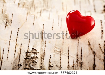 Colorful red Valentines heart on natural bark symbolic of love, romance and relationships, corner decoration with copy space for your message