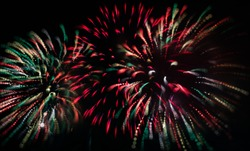 Colorful Red, White, and Green Fireworks Against Dark Sky