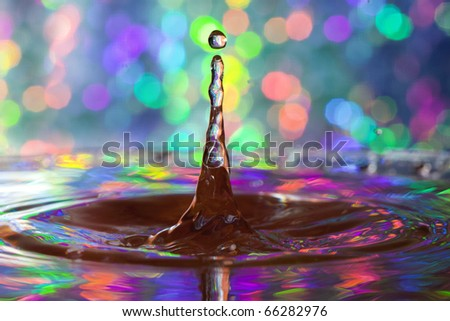 Colorful red, yellow, pink green and blue water drop and splash with reflections of colorful background in drop