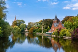 Colorful reflections of trees in the water in Minnerwater park. Bruges, Belgium. Love lake, brick church and autumn park in Brugge.