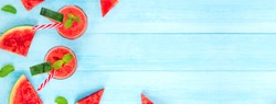 Colorful refreshing drinks for summer, cold watermelon juice smoothies in the glasses on light blue wood banner background with copy space