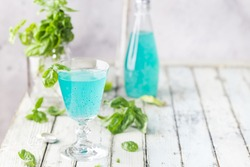 Colorful refreshing summer drink with basil seeds on light background.