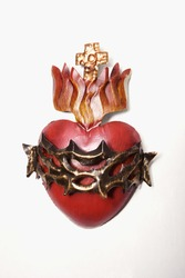 Colorful religious wall art depicting a heart, a crown of thorns, a flame and a cross. Isolated on white. Vertical shot.