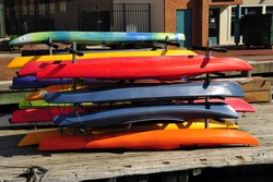 Colorful rental kayaks are stacked on the dock, Inner Harbor, Baltimore, MD
