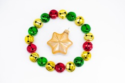Colorful ringing Christmas bells in gold, red and green. In shape of circle with golden star christmas decoration in the middle. The concept of Christmas. Holiday background
