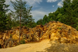colorful rocks in the Rudawy Landscape Park by the yellow and purple lake in the old pyrite mines