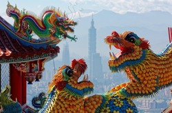 Colorful roofs of a Taiwanese temple decorated with sculptures of sacred & auspicious animals ( dragons & lions) in traditional mosaic art & Taipei 101 Tower in background in Taipei City Taiwan, Asia