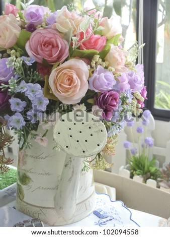 colorful rose flower in watering cans