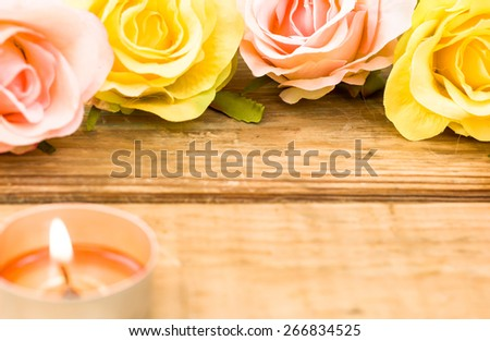 Colorful roses and candle among roses on wood background useful as esoteric backgrounds