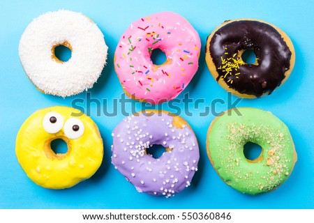 Colorful round donuts on blue background. Flat lay, top view.