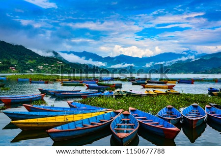 Colorful row boats docked on Lake Phewa in Pokhara, Nepal.