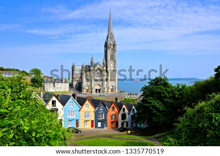 Colorful row houses with towering cathedral in background in the port town of Cobh, County Cork, Ireland