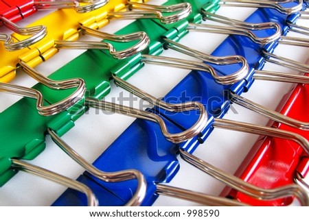 Colorful rows of large paper clips or binding clips.