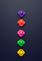 Colorful rubber ducks aligned in a line over dark grey background, above view