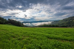 Colorful rural panoramic landscape image with a wide view over fields,forest,hills and foggy valleys towards the horizon and a blue sky with clouds