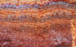 colorful rusty metal surface divided into layers or strata as geological creating organic shapes - worn abstract background for a wallpaper