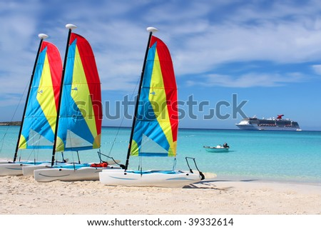 Colorful sailboats and motorboat, on a tropical beach at Half Moon Cay in the Bahamas with cruise ship in background on a tropical beach at Half Moon Cay in the Bahamas